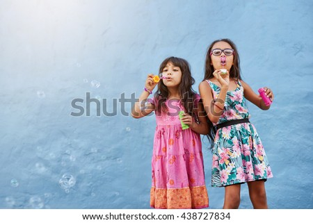 Portrait of adorable little girls blowing soap bubbles against blue wall. Two young girls playing together. - stock photo