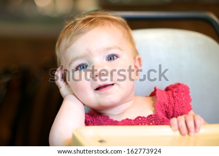 Portrait of adorable little toddler girl sitting in a high chair. - stock photo