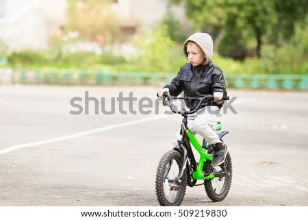 portrait of adorable little urban boy wearing black leather jacket. City style. Urban kids. The boy learns to ride a bike. Child driving a bicycle.