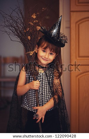 Portrait of adorable little witch with broom. Halloween costume. With some grain - stock photo