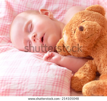 Portrait of adorable newborn baby sleeping on cute pink pillow with soft toy of teddy bear, day dreaming, love and childcare concept  - stock photo