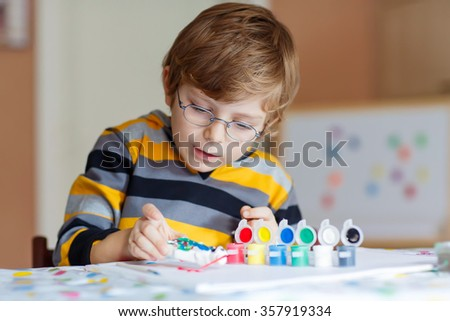 Portrait of adorable preschool kid boy with glasses at home making homework. Little child drawing with colorful watercolors and gouache, indoors. School, education concept