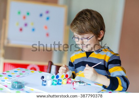 Portrait of adorable preschool kid boy with glasses at home making homework. Little child drawing with colorful watercolors and gouache, indoors. School, education concept - stock photo