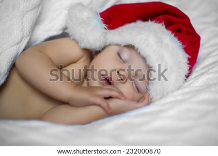 portrait of adorable quite beautiful girl sleeping in christmas hat on white blanket - stock photo
