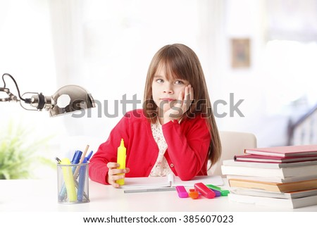 Portrait of adorable school girl sitting at desk and dreaming while coloring colorful pen.