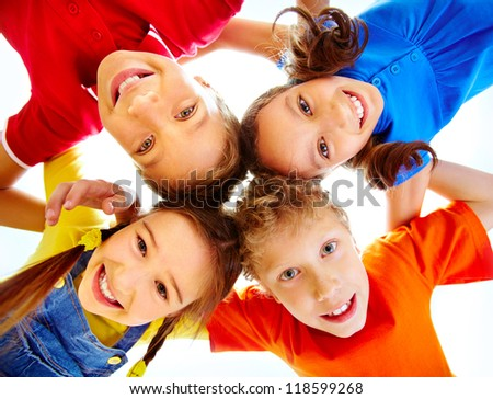 Portrait of adorable schoolkids touching their heads and looking at camera - stock photo