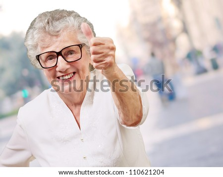 portrait of adorable senior woman doing good gesture at city - stock photo