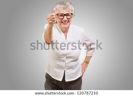 portrait of adorable senior woman doing good gesture over grey - stock photo