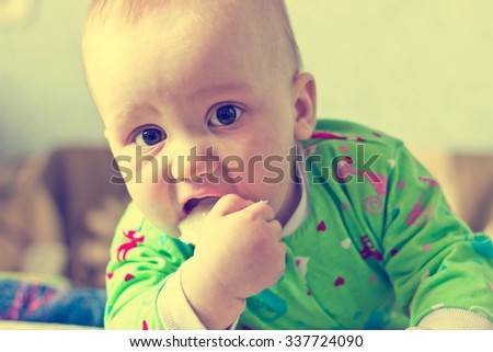 Portrait of adorable serious baby boy eating cabbage and looking at camera. Close up. Image with vintage filter