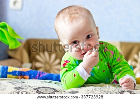 Portrait of adorable serious baby boy eating cabbage and looking at camera. Horizontal image - stock photo