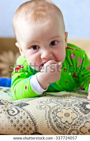 Portrait of adorable serious baby boy eating cabbage and looking at camera. Vertical image