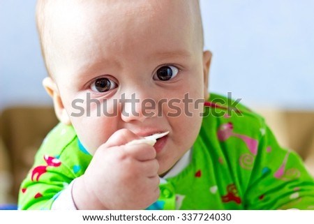 Portrait of adorable serious baby boy eating cabbage and looking at lens. Close up - stock photo