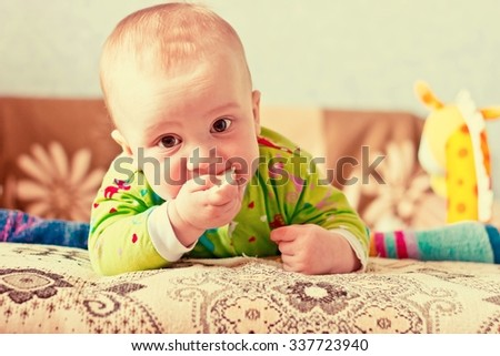 Portrait of adorable serious baby boy eating cabbage and looking at lens. Horizontal image with vintage effect filter - stock photo