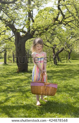 portrait of adorable small blond girl in preschool age standing with picnic basket and green apple outdoors on green meadow - stock photo