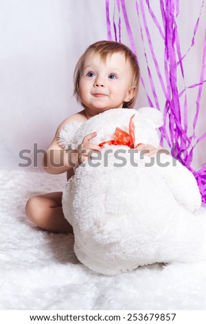 portrait of adorable smiling girl with bear toy on white and purple decorations background