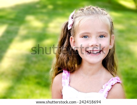 Portrait of adorable smiling little girl in the park outdoor - stock photo