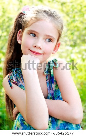 Portrait of adorable smiling little girl outdoor in summer day