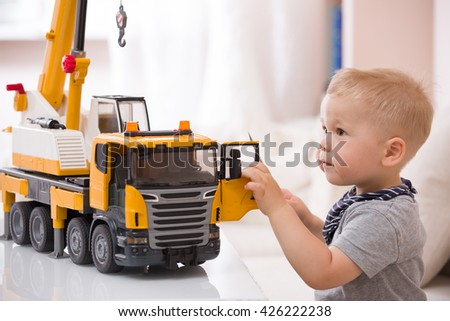Portrait of adorable smiling toddler boy sitting at the table playing with a big construction car at home. Little child with toy car. Educative toys for children. Early learning and developing concept - stock photo