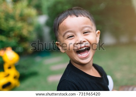 Portrait of adorable toddler Asian little boy looking into something and happy in the garden Education concept.