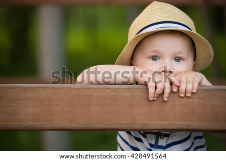 Portrait of adorable toddler boy standing at wooden fence and looking into distance. Cute child in a straw hat watching animals. Boy walking in the park. Lifestyle concept. - stock photo