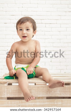 portrait of adorable toddler sitting on wooden box with white walls on background - stock photo