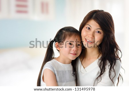 Portrait of adorable young girl and mother at home. Happy Asian family. - stock photo