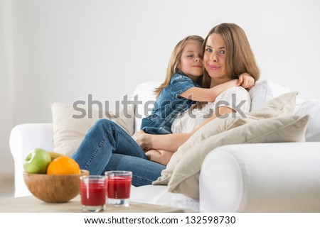 Portrait of adorable young girl and mother embracing at home - stock photo