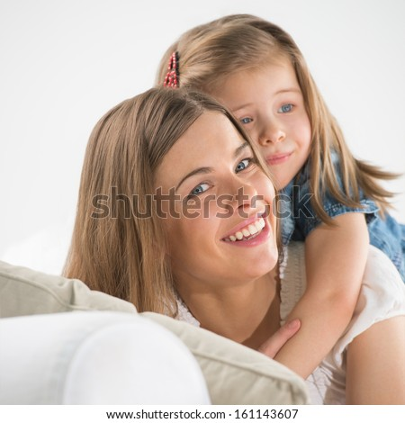 Portrait of adorable young girl and mother in a playful mood at home