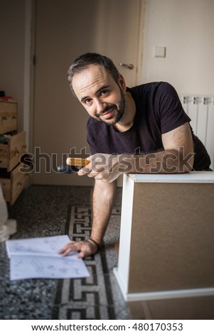 Portrait of adult bearded man holding screwdriver and instructions for assembling furniture looking at camera