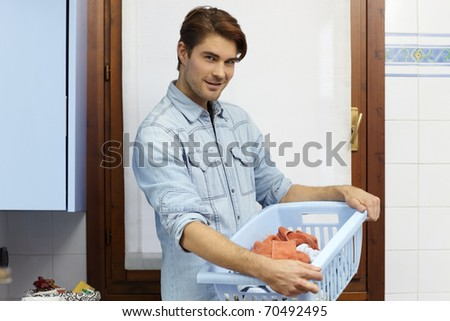 portrait of adult caucasian man looking at camera with clothes basket. Horizontal shape, side view