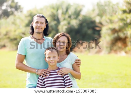 Portrait of adult couple with teenage son enjoying time in sunny park