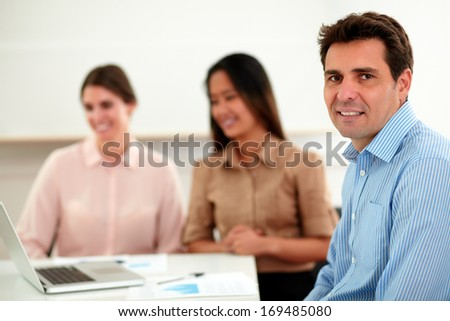 Portrait of adult hispanic man on blue shirt smiling and looking at you while sitting in front of two pretty coworkers on office