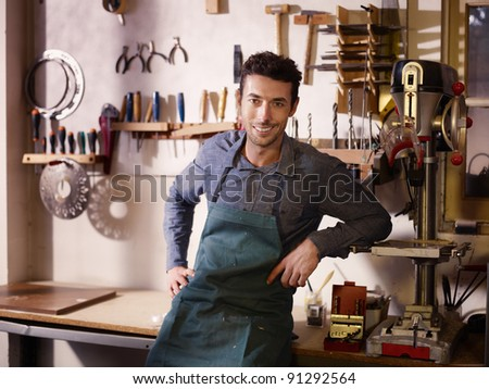 Portrait of adult italian man at work as craftsman in shop with tools in background