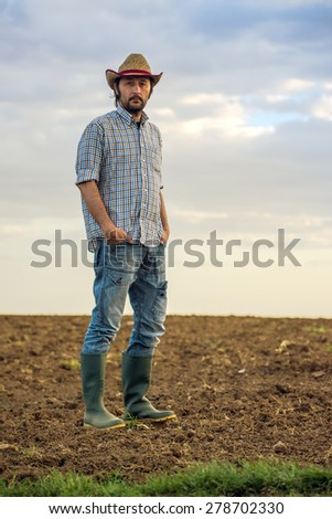 Portrait of Adult Male Farmer Standing on Fertile Agricultural Farm Land Soil, Looking into Camera - stock photo