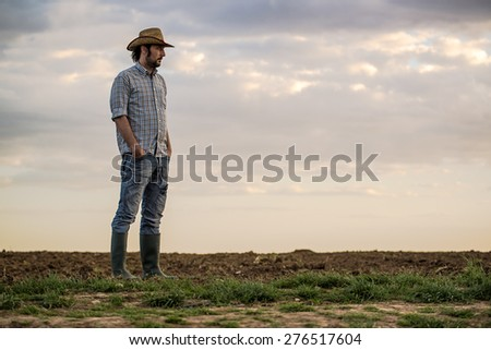 Portrait of Adult Male Farmer Standing on Fertile Agricultural Farm Land Soil,Looking into Distance. - stock photo