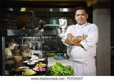 Portrait of adult man at work as chef in the kitchen of an Asian restaurant, posing with arms crossed