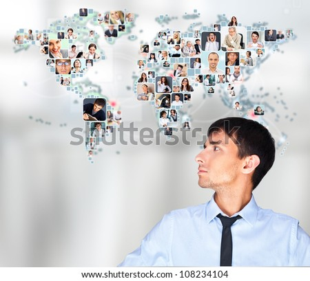 Portrait of adult man communicating with his friends across the world. Standing against world map with photo of people. International communications concept - stock photo