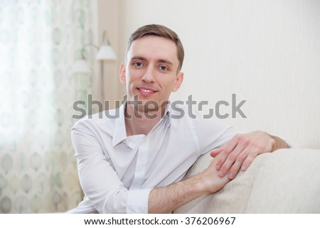 Portrait of   adult  man sitting on   couch in   living room.