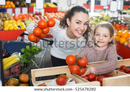 Portrait of adult mom and little girl purchasing greenhouse-grown tomato