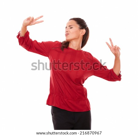 Portrait of adult pretty brunette on red shirt with victory sign and eyes closed celebrating her victory while standing on isolated studio