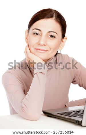 Portrait of  adult smiling business woman sitting in front of laptop computer. Isolated white background.