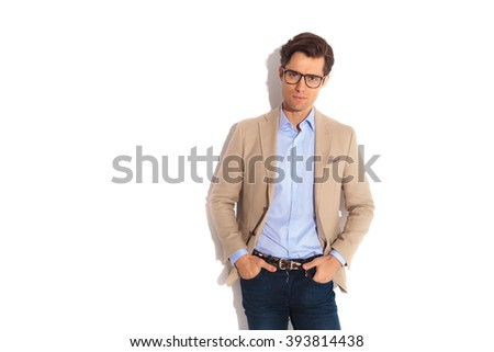 portrait of adult wearing jeans and glasses while posing looking at the camera with both hands in pockets in isolated studio background. - stock photo