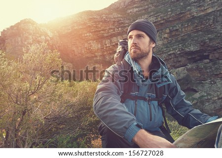 portrait of adventure man with map and extreme explorer gear on mountain with sunrise or sunset - stock photo