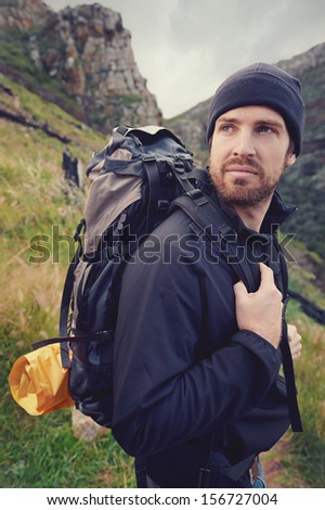 Portrait of adventure trekking man in mountains with backpack