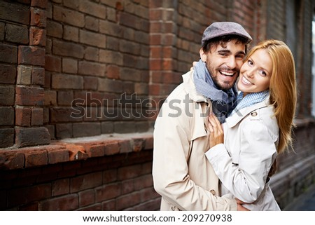 Portrait of affectionate couple in stylish clothes looking at camera outside - stock photo