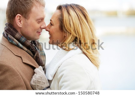 Portrait of affectionate couple touching by their noses - stock photo