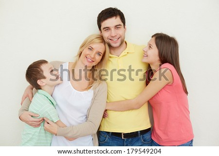 Portrait of affectionate family of four posing over white background - stock photo