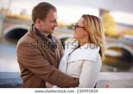 Portrait of affectionate man and woman in embrace looking at one another outside - stock photo