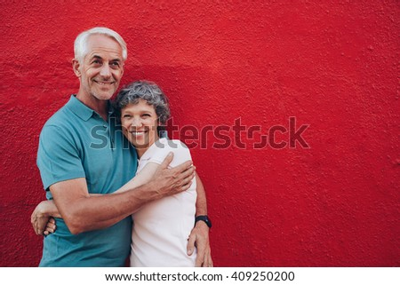 Portrait of affectionate mature couple embracing against red background. Loving mature couple standing together with copy space. - stock photo