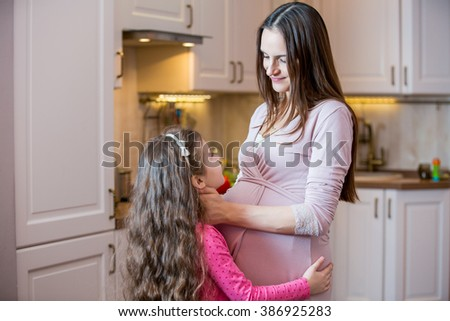 Portrait Of Affectionate Mother And Daughter At Home. Pregnant mother looking at each other's eyes